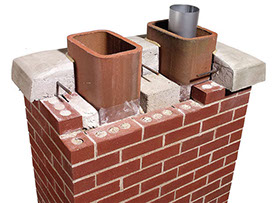 This photo shows a chimney with a section cut out to make the different parts of the chimney visable. The flues are seen inside the bricks & cap