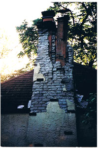 Chimney before repair. Bricks are crumbling and the top half of the flues are visible. Huge cracks down the remaining portion of chimney.