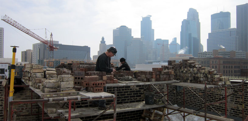 A view from a rootop downtown Minneapolis as Tim and his crew make repairs. Minneapolis skyline in the background.