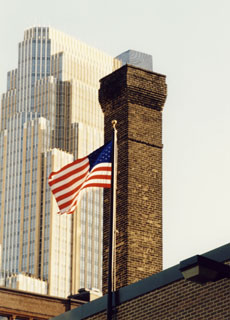 A chimney downtown that we repaired the top several courses and tuckpointed the remainder of the chimney. American flag in foreground.